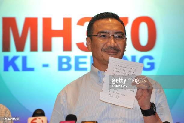Malaysia's Minister of Defence and acting Minister of Transport Hishammuddin Hussein shows a note of latest information from Chinese officials during...