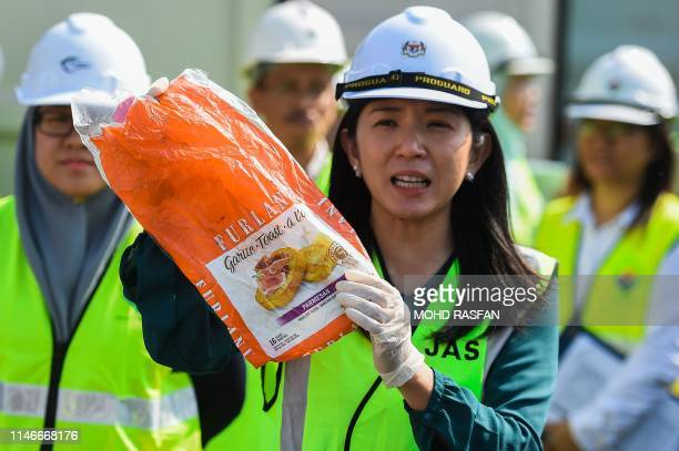 Malaysia's Minister of Energy Science Technology Environment and Climate Change Yeo Bee Yin shows a sample of plastic waste shipment before sending...