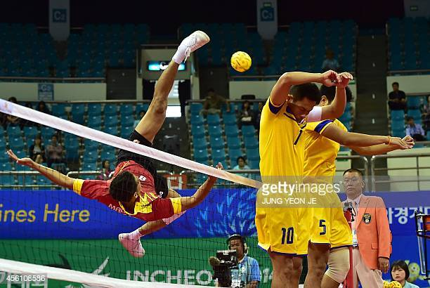 Malaysia's Mohamad Fadzli Bin Muhammad Roslan strikes the ball as Thailand's Suriyan Peachan and Pomchai Kaokaew try to block the ball in the men's...