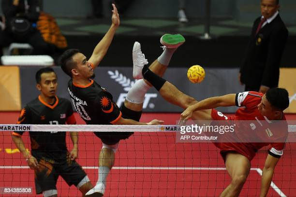 Malaysia's Mohd Hanafiah hits the ball past Mohd Aliffuddin Jamaludin of Brunei during their men's Sepaktakraw team Regu roundrobin match of the 29th...