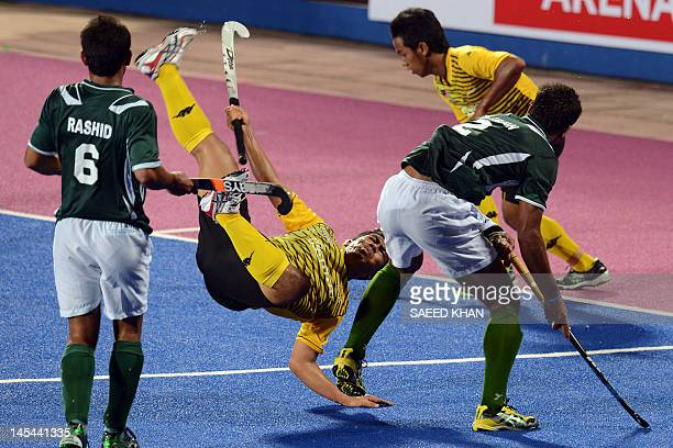 Malaysia's Mohd Shahrun Nabil Abdullah falls to the ground as Pakistan defenders Rashid Mehmood and Muhammad Irfan block his attack during their...