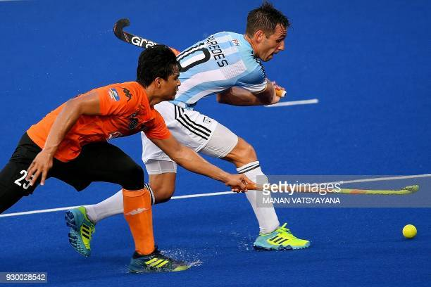 Malaysia's Najmi Jazlan vies for the ball with Matias Paedes of Argentina during their men's field hockey thirdfourth place match of the 2018 Sultan...