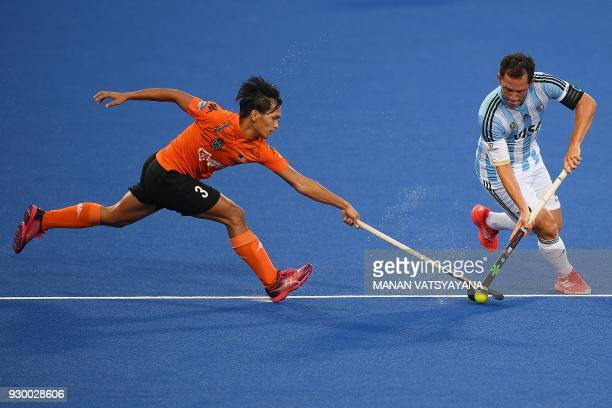 Malaysia's Norsyafiq Sumantri vies for the ball with Pedro Ibarra of Argentina during their men's field hockey thirdfourth place match of the 2018...