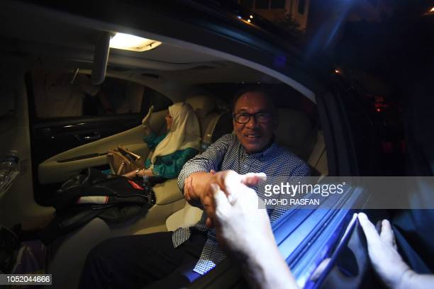 TOPSHOT Malaysia's People's Justice Party president and leader of the Pakatan Harapan coalition Anwar Ibrahim shakes hands with supporters as his...