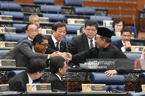Malaysia's People's Justice Party president and leader of the Pakatan Harapan coalition Anwar Ibrahim shakes hands with other members after taking...
