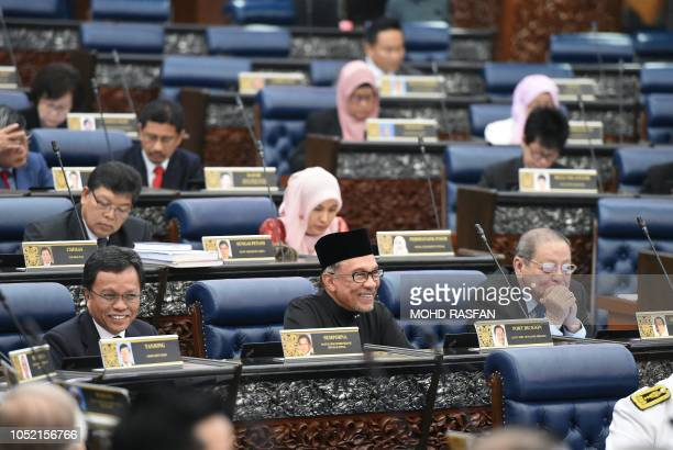 Malaysia's People's Justice Party president and leader of the Pakatan Harapan coalition Anwar Ibrahim smiles as he sits with other members after...