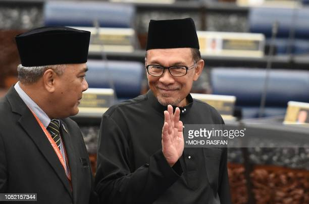 Malaysia's People's Justice Party president and leader of the Pakatan Harapan coalition Anwar Ibrahim waves before taking an oath as a member of the...