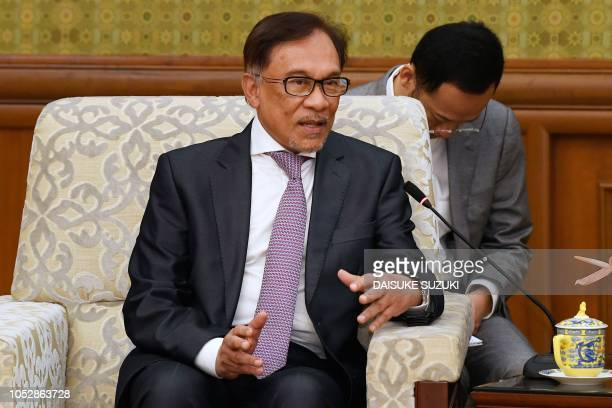 Malaysia's People's Justice Party president and leader of the Pakatan Harapan coalition Anwar Ibrahim speaks to China's Foreign Minister Wang Yi...