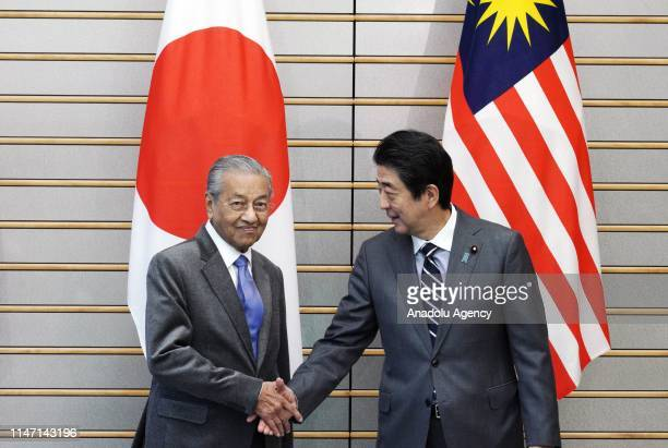Malaysia's Prime Minister Mahathir Mohamad shakes hands with Japan's Prime Minister Shinzo Abe at the start of their meeting at Abe's official...