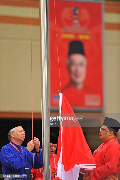 Malaysia's Prime Minister Najib Razak hoists the party flag during an annual general assembly in Kuala Lumpur on December 1 2011 The ruling party...