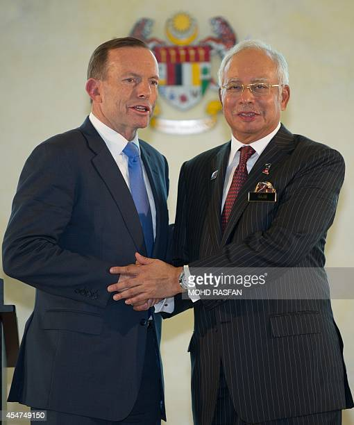 Malaysia's Prime Minister Najib Razak shakes hands with his Australian counterpart Tony Abbott after a joint press conference at the prime minister's...