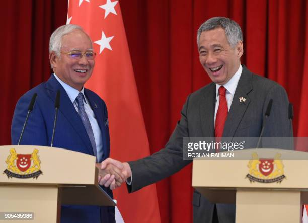Malaysia's Prime Minister Najib Razak shakes hands with his Singaporean counterpart Lee Hsien Loong after a joint press conference at the 8th...