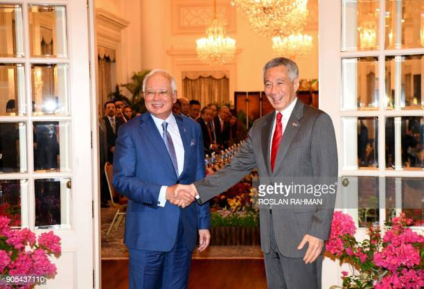 Malaysia's Prime Minister Najib Razak shakes hands with his Singaporean counterpart Lee Hsien Loong during the 8th SingaporeMalaysia leaders retreat...