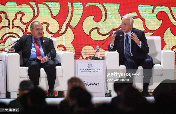 Malaysia's Prime Minister Najib Razak speaks as Papua New Guinea's Prime Minister Peter O'Neill looks on during a dialogue on the final day of the...