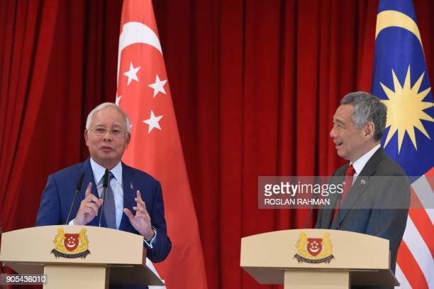 Malaysia's Prime Minister Najib Razak speaks whilst his Singaporean counterpart Lee Hsien Loong reacts during a joint press conference at the 8th...