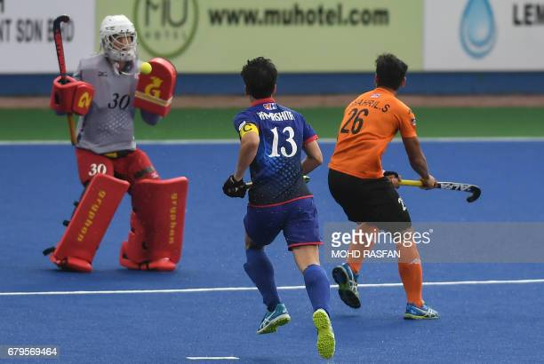 Malaysia's Shahril Saabah hits the ball as Japan's goalkeeper Suguru Shimmoto makes a save during their 5th and 6th placing match of the 2017 Sultan...