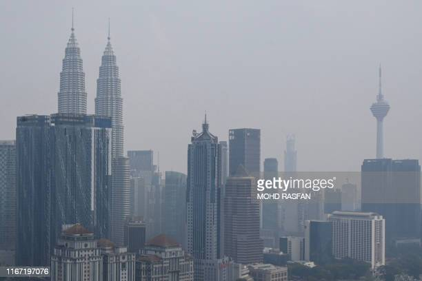 Malaysias skyline with landmark Petronas Twin Towers and Kuala Lumpur Tower are seen shrouded in haze in Kuala Lumpur on September 10 2019 Hundreds...