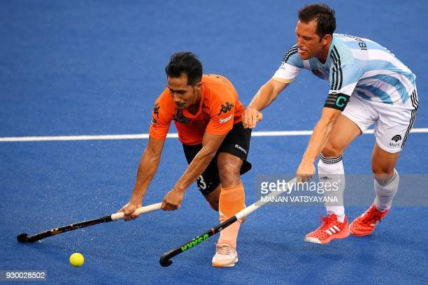 Malaysia's Tengku Tajuddin vies for the ball with Pedro Ibarra of Argentina during their men's field hockey thirdfourth place match of the 2018...