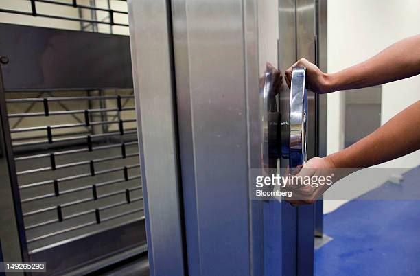 A MalcaAmit Global Ltd security guard demonstrates for a photograph how a vault is secured at the company's new gold storage facility in Hong Kong...