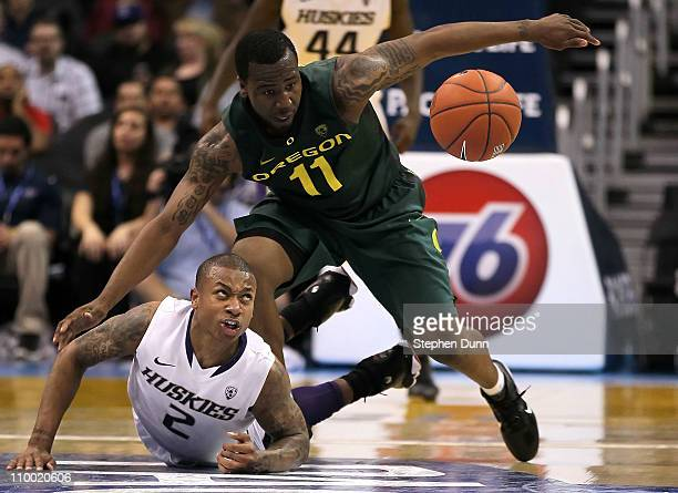 Malcolm Armstead of the Oregon Ducks and Isaiah Thomas of the Washington Huskies battle for a loose ball in the second half in the semifinals of the...