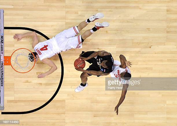 Malcolm Armstead of the Wichita State Shockers goes up for a shot against Aaron Craft and Shannon Scott of the Ohio State Buckeyes during the West...