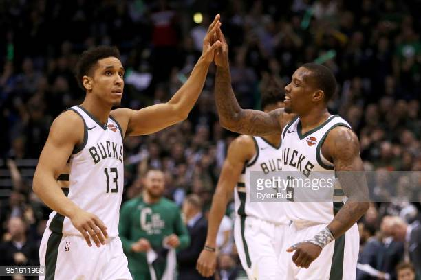 Malcolm Brogdon and Eric Bledsoe of the Milwaukee Bucks celebrate in the fourth quarter against the Boston Celtics during Game Six of Round One of...