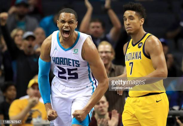 Malcolm Brogdon of the Indiana Pacers watches as PJ Washington of the Charlotte Hornets reacts after a play during their game at Spectrum Center on...