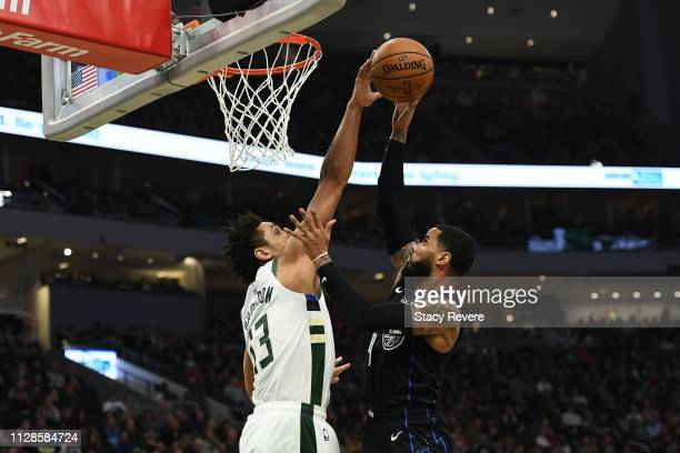 Malcolm Brogdon of the Milwaukee Bucks blocks a shot by DJ Augustin of the Orlando Magic during the second half of a game at Fiserv Forum on February...