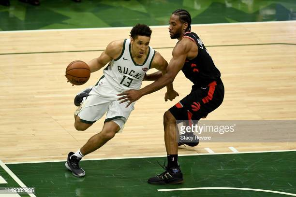 Malcolm Brogdon of the Milwaukee Bucks dribbles the ball while being guarded by Kawhi Leonard of the Toronto Raptors in the second quarter in Game...