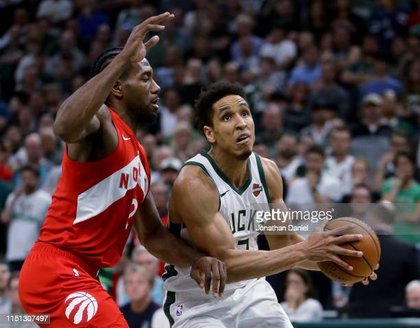 Malcolm Brogdon of the Milwaukee Bucks dribbles the ball while being guarded by Kawhi Leonard of the Toronto Raptors in the fourth quarter during...