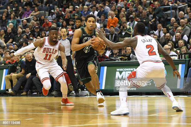 Malcolm Brogdon of the Milwaukee Bucks drives between David Nwaba and Jerian Grant of the Chicago Bulls during a game at the Bradley Center on...