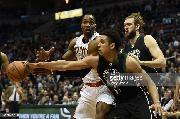 Malcolm Brogdon of the Milwaukee Bucks fouls Dwight Howard of the Atlanta Hawks while reaching for the ball during the first half of a game at the...