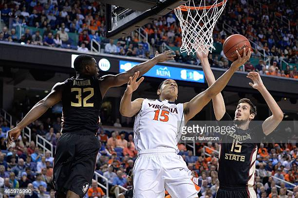Malcolm Brogdon of the Virginia Cavaliers drives between Montay Brandon and Boris Bojanovsky of the Florida State Seminoles during the quarterfinals...
