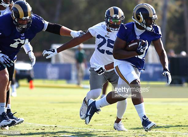 Malcolm Brown of the Los Angeles Rams runs past TJ McDonald during practice on August 3 2016 in Irvine California