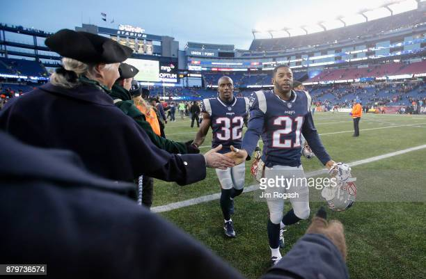 Malcolm Butler and Devin McCourty of the New England Patriots high fives members of the End Zone Militia after a game against the Miami Dolphins at...