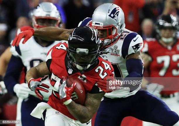 Malcolm Butler of the New England Patriots attempts to tackle Devonta Freeman of the Atlanta Falcons in the first quarter of Super Bowl 51 at NRG...