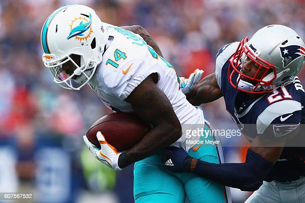 Malcolm Butler of the New England Patriots attempts to tackle Jarvis Landry of the Miami Dolphins during the second half at Gillette Stadium on...