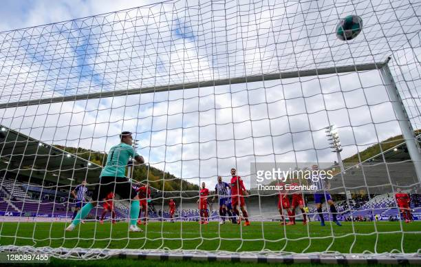 Malcolm Cacutalua of Aue scores his team's first goal past goalkeeper Kevin Mueller of Heidenheim during the Second Bundesliga match between FC...