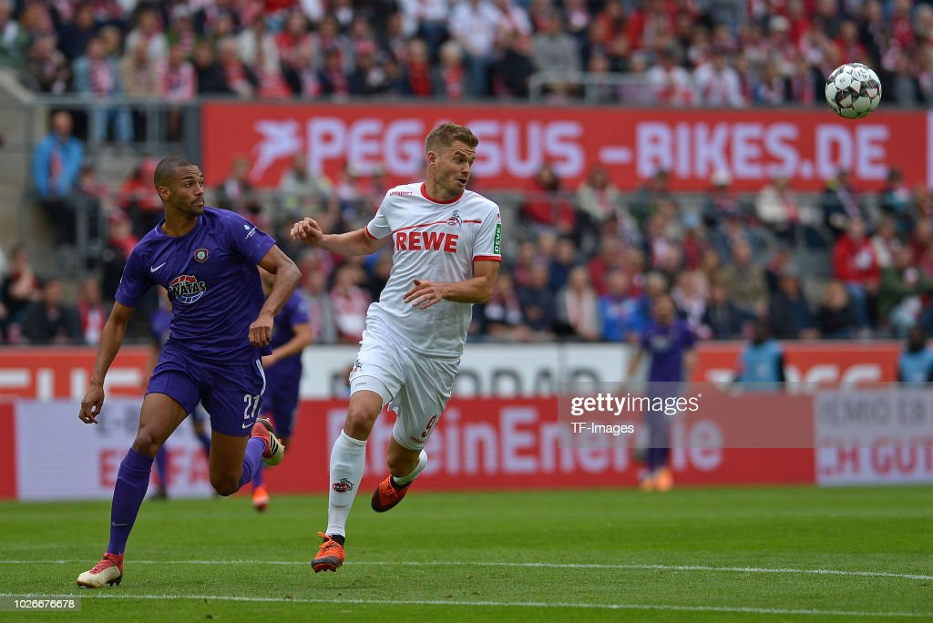 Malcolm Cacutalua of Erzgebirge Aue and Simon Terodde of FC Koeln battle for the ball during the second Bundesliga match between FC Koeln and FC Erzgebirge Aue at RheinEnergieStadion on August 25, 2018 in Cologne, Germany.