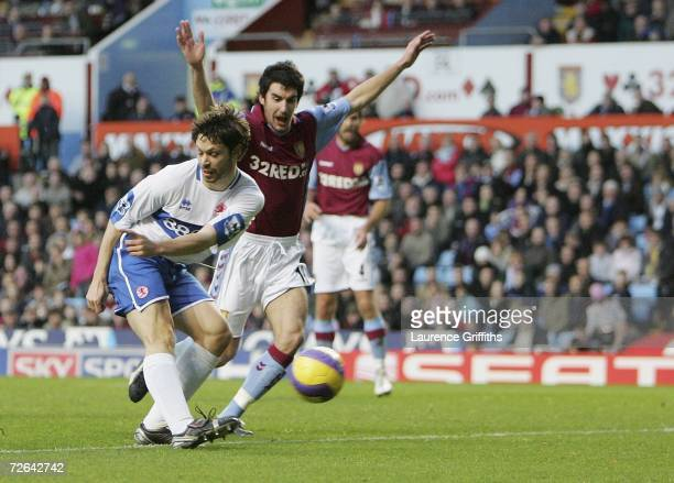Malcolm Christie of Middlesbrough scores the opening goal under pressure from Liam Ridgewell of Villa during the Barclays Premiership match between...