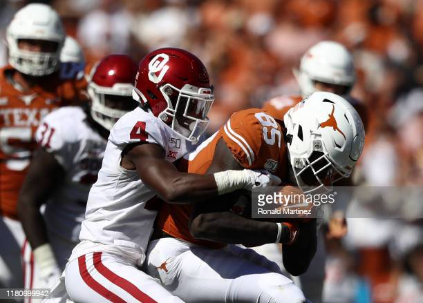 Malcolm Epps of the Texas Longhorns is tackled by Jaden Davis of the Oklahoma Sooners during the 2019 AT&T Red River Showdown at Cotton Bowl on...