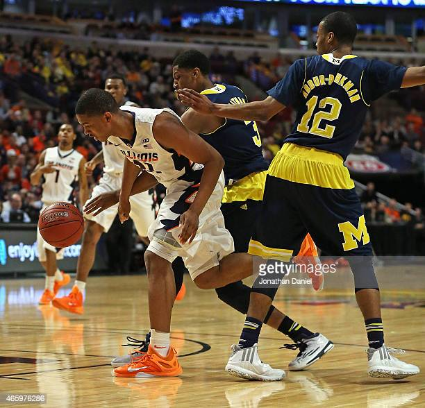 Malcolm Hill of the Illinois Fighting Illini drives between Kameron Chatman and Muhammad-Ali Abdur-Rahkman of the Michigan Wolverines during the...