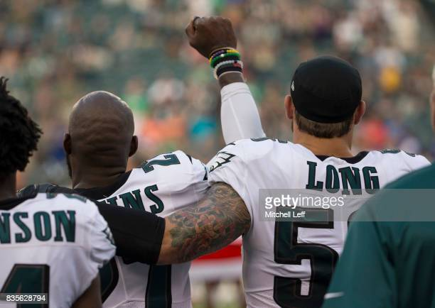 Malcolm Jenkins of the Philadelphia Eagles holds his fist in the air during the national anthem while Chris Long of the Philadelphia Eagles puts his...