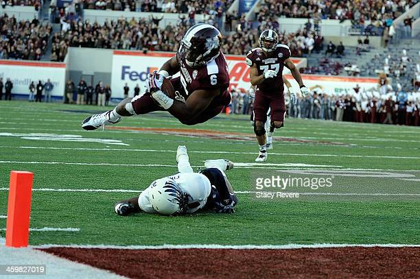 Malcolm Johnson of the Mississippi State Bulldogs dives for a touchdown over Jaylon Finner of the Rice Owls during the 55th annual AutoZone Liberty...