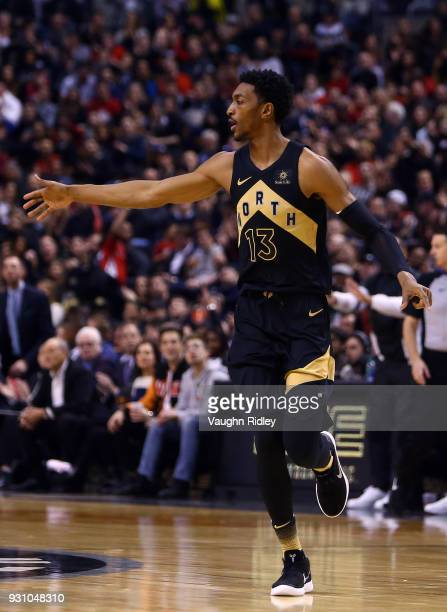 Malcolm Miller of the Toronto Raptors high fives a teammates during the first half of an NBA game against the Houston Rockets at Air Canada Centre on...