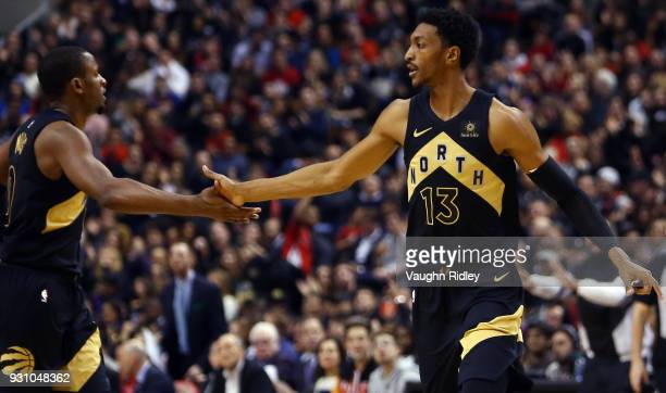 Malcolm Miller of the Toronto Raptors high fives CJ Miles during the first half of an NBA game against the Houston Rockets at Air Canada Centre on...