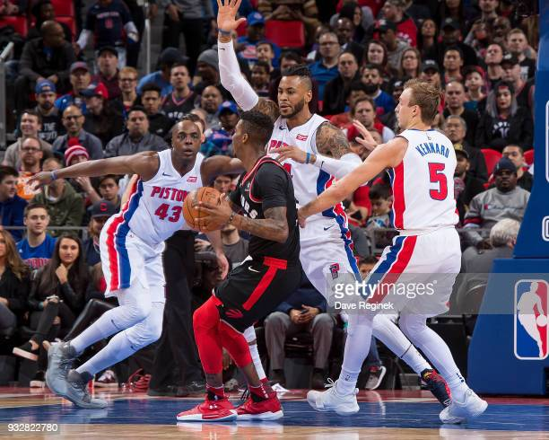 Malcolm Miller of the Toronto Raptors is surrounded by Eric Moreland Anthony Tolliver and Luke Kennard of the Detroit Pistons in the first half of an...