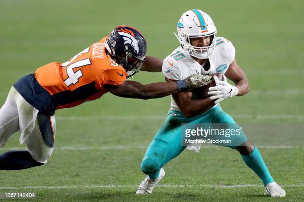 Malcolm Perry of the Miami Dolphins is tackled by Essang Bassey of the Denver Broncos after his catch during the fourth quarter at Empower Field At...