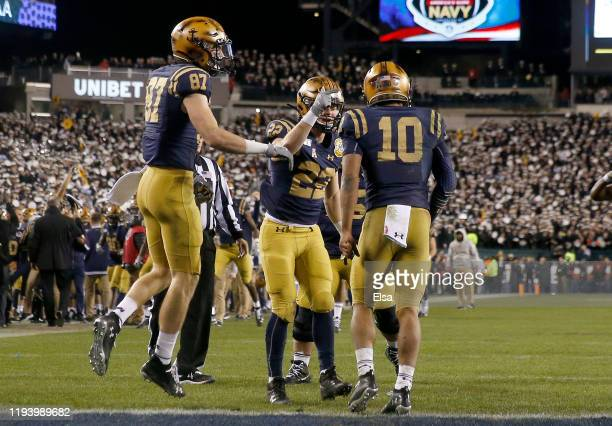 Malcolm Perry of the Navy Midshipmen celebrates his touchdown with teammates Ryan Mitchell and Myles Fells in the fourth quarter against the Army...