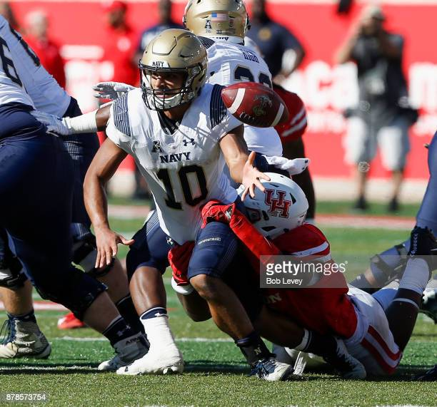 Malcolm Perry of the Navy Midshipmen flips the ball just as he his tackled by a Houston Cougars defender in the fourth quarter on November 24 2017 in...